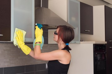 Teenage girl cleaning kitchen cabinet