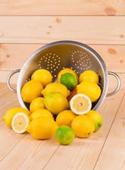 Citrus fruits in colander on wood.