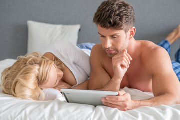 Handsome man lying in bed reading on a tablet