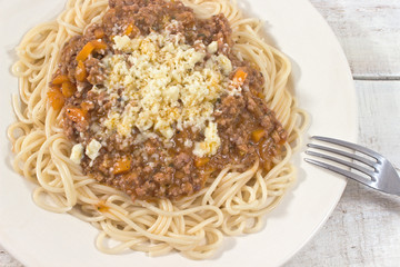 Spaghetti bolognese on plate with fork on wooden background