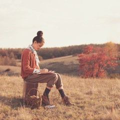 Hipster girl drawing in the fall outdoors