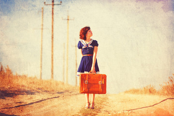 Beautiful brunette girl with suitcase on the countryside road.