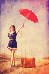 Beautiful brunette girl with suitcase and umbrella on the countr