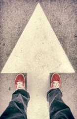 Shoes and forward arrow sign from above