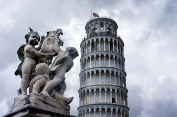 Statues of cherubs angel and Leaning Tower in Pisa, Italy