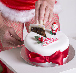 Santa's helper cutting slice of Christmas cake