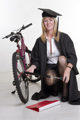 university student in cap and gown pumping tire of her bicycle