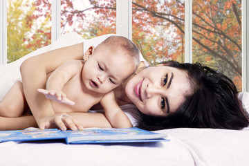 Asian mother and her baby girl on bed