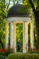 Beautiful autumn park composition with the girl in an arbor