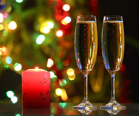glasses with champagne and candle against festive lights