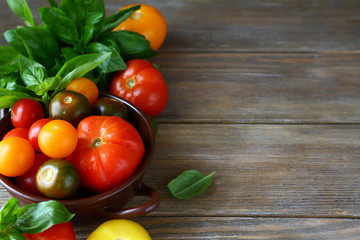 wooden background with tomatoes and basil