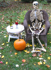 Halloween skeleton relaxes with glass of wine