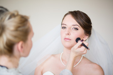 Stylist making up beautiful bride before wedding