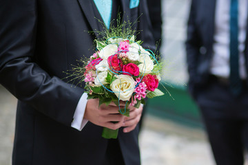 Groom holding wedding bouquet of his bride
