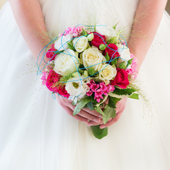 Young bride holding beautiful wedding bouquet