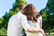 canvas print picture - Paar sitzt umarmt in Sonne auf Park Wiese
