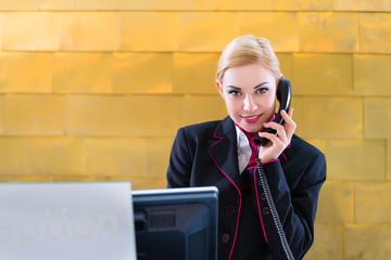 Hotel Rezeptionistin telefoniert mit Gast