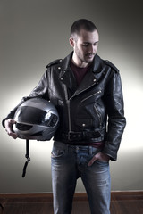 Biker in leather jacket and sunglasses posing holding his helmet