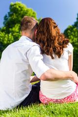 Paar sitzt umarmt in Sonne auf Park Wiese