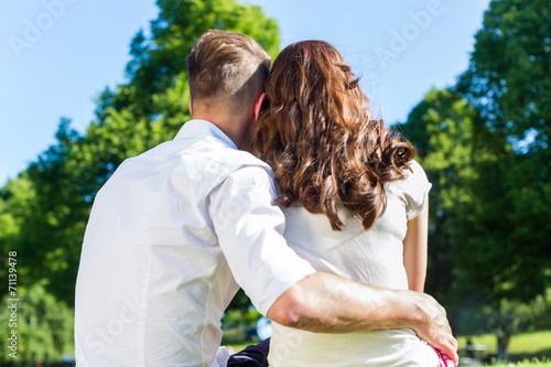 canvas print picture Paar sitzt umarmt in Sonne auf Park Wiese
