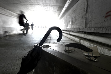 Suitcase and umbrella n an underpass