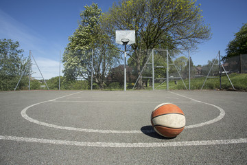Used basketball on an empty outdoor basketball court