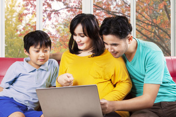 Hispanic family using laptop on sofa