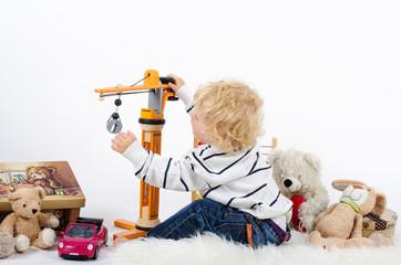 Kleinkind mit viel Spielzeug