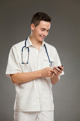 Smiling doctor using mobile phone