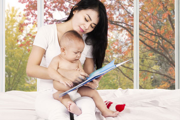 Mother and her baby read story book