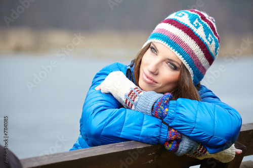 canvas print picture Smiling beautiful young woman relaxing outdoor in a winter day