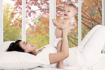 Playful mother with her baby on bedroom