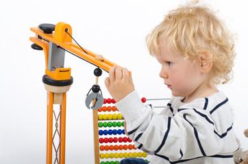 Kleiner Junge spielt mit Holzkran