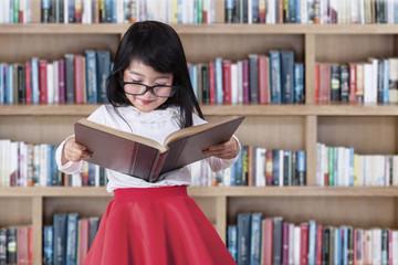 Schoolgirl reads book in library