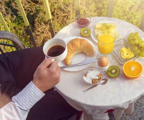 Mann trinkt Kaffe am Frühstückstisch auf dem Balkon