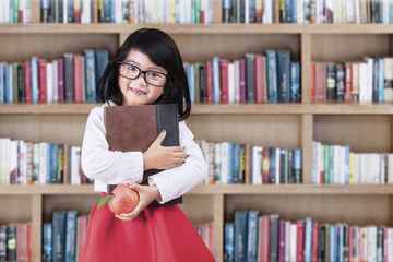 Schoolgirl with a book and apple in library