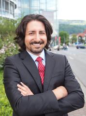 Türkischer Geschäftsmann im Anzug vor dem Office