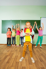 Boy stands in front of children with hands up