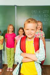 Boy stands in front of kids near blackboard