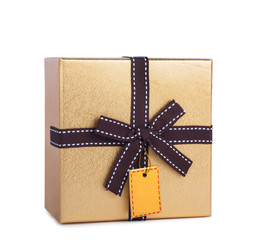 Beautiful gift box in gold paper with bow and label isolated on