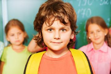Portrait of boy with yellow bag near chalkboard