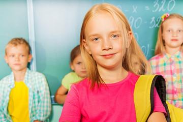 Girl wears bag near blackboard, pupils behind her