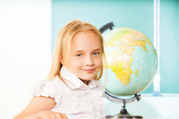 Blond girl portrait with globe and blackboard