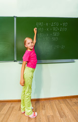 Girl with chalk in hand writing equation