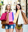 two smiling girls with shopping bags walking