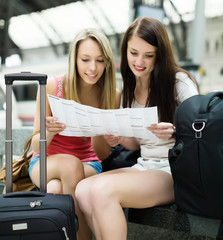 girls sitting at railroad station with map