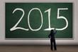 Woman writes number 2015 on blackboard