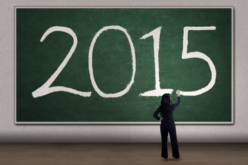 Woman writes number 2015 on blackboard