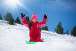 Happy girl sitting on sled on sunny day