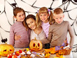 Family  with child holding make carved pumpkin.